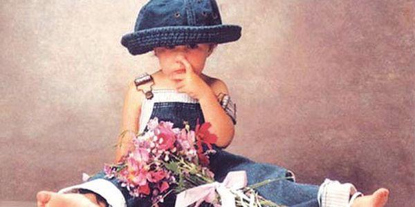 Pohlednice Anne Geddes holka s kytkou a prst v nose