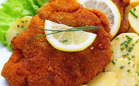 Kuřecí a vepřové řízky, máslové brambory a zeleninový salát v restauraci Švejk v Praze.