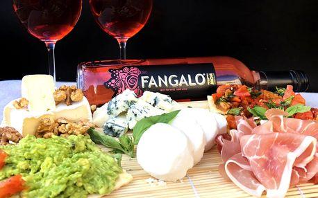 Prkénko plné delikates a láhev vína Fangalo